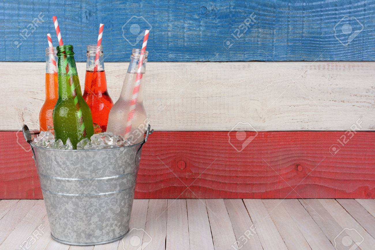 A bucket of soda bottles with drinking straws against a red, white and blue background for a 4th of July picnic, with copy space. - 39041525