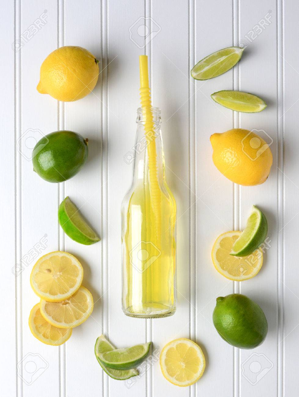 Lines and Lemons surrounding a bottle of soda on a white bead board table. High angle shot in vertical format. - 40937028