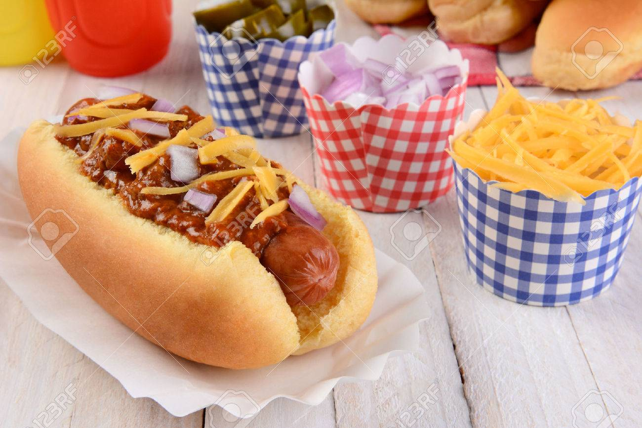 Closeup of a grilled chili dog with cheese and onions on a rustic..