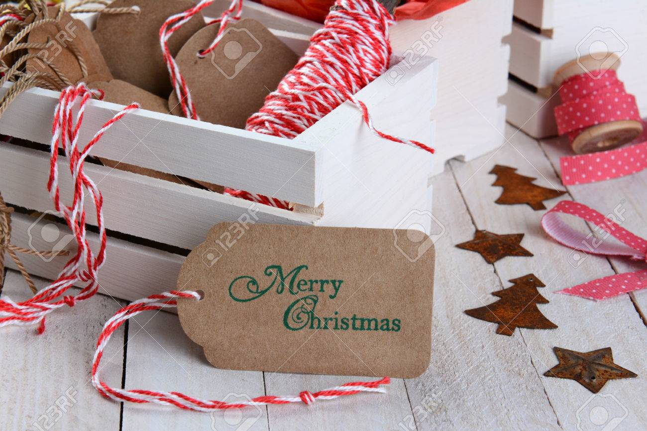 Closeup Of A Christmas Gift Tag Leaning On A Wood Box Of Wrapping ...