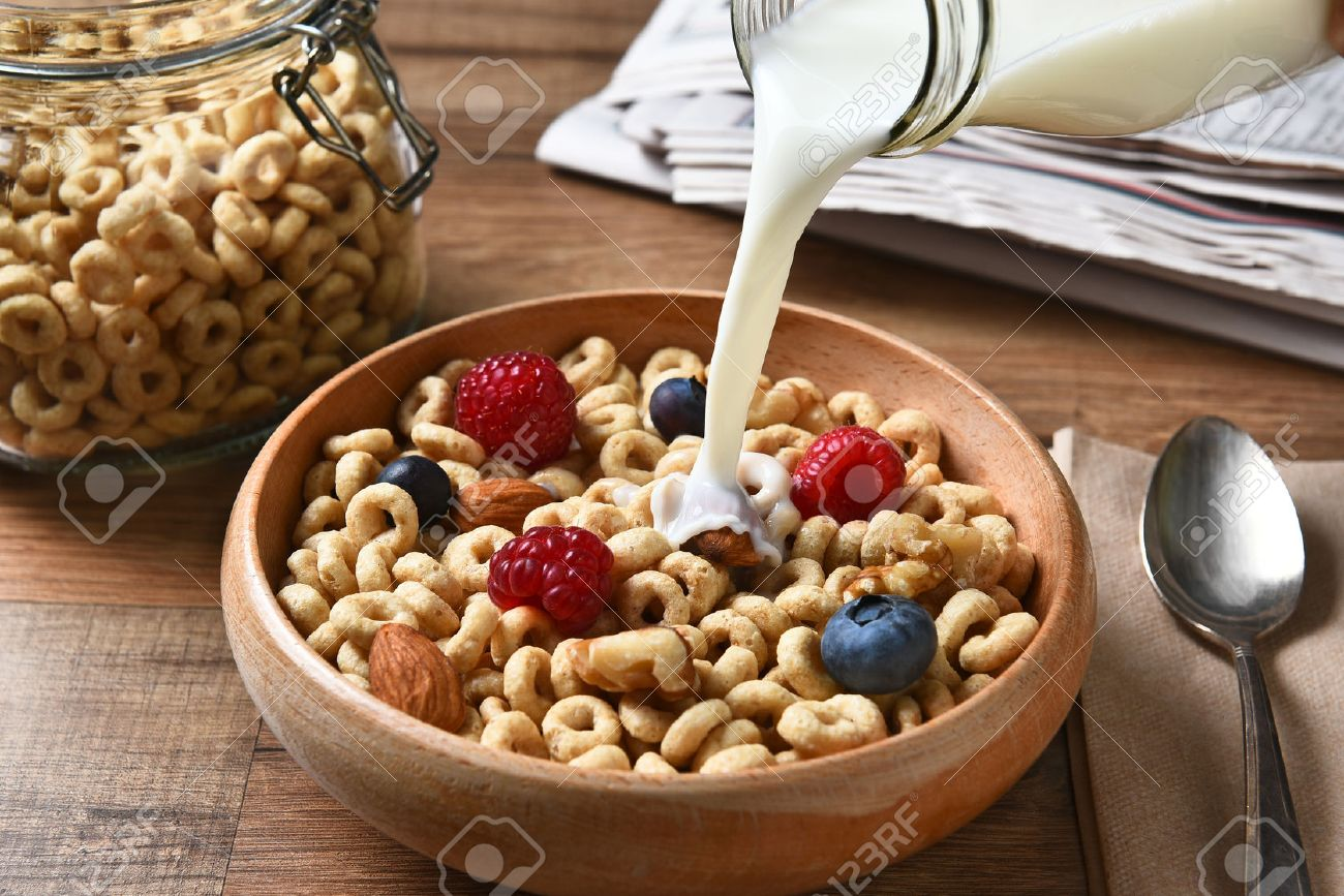 High angle view of a bowl of breakfast cereal with blueberries, raspberries and nuts. A bottle of milk is pouring into the bowl - 51229229