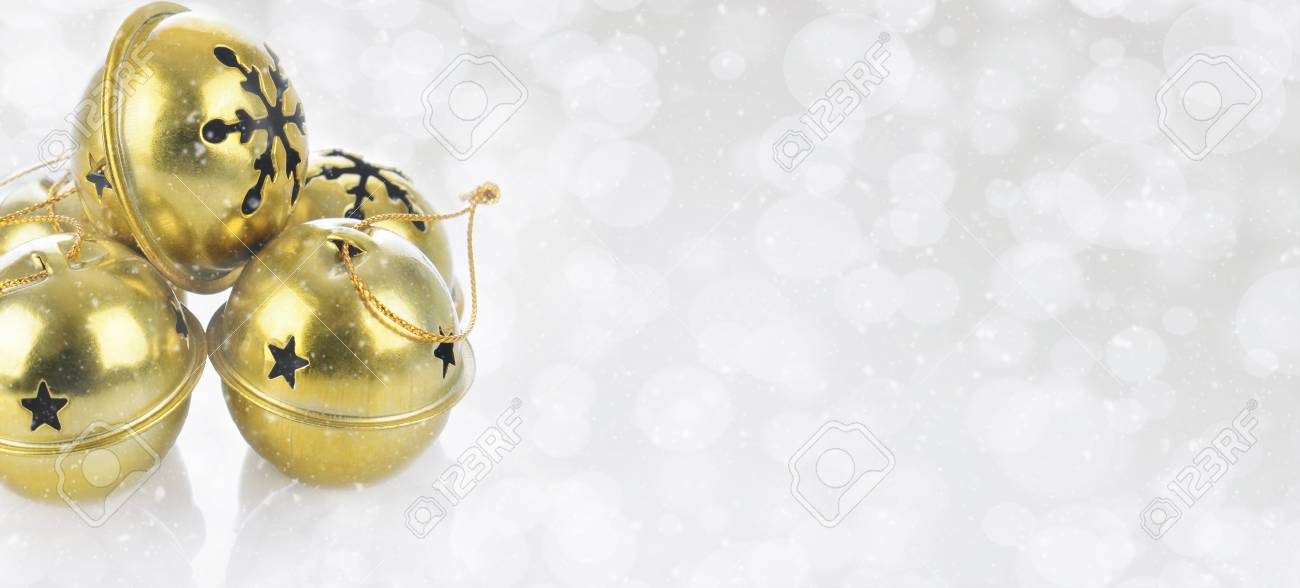 Christmas Concept: Gold Jingle bells on a snowy bokeh silver background with copy space. - 110251010