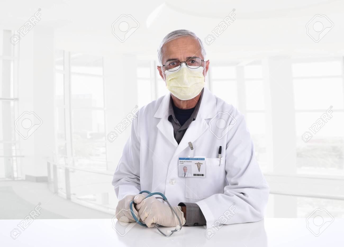 Medical Professional wearing a surgical mask, gloves and holding a stethoscope in a modern office setting. ID Badge is computer generated. - 150563435