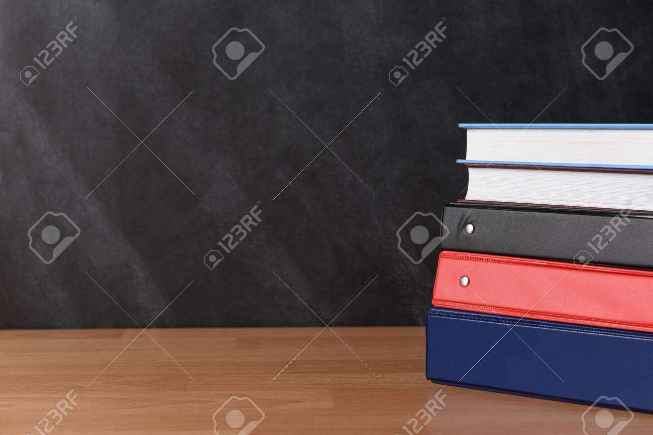 A stack of three different binders on desk in front of black board with two books. - 156353808