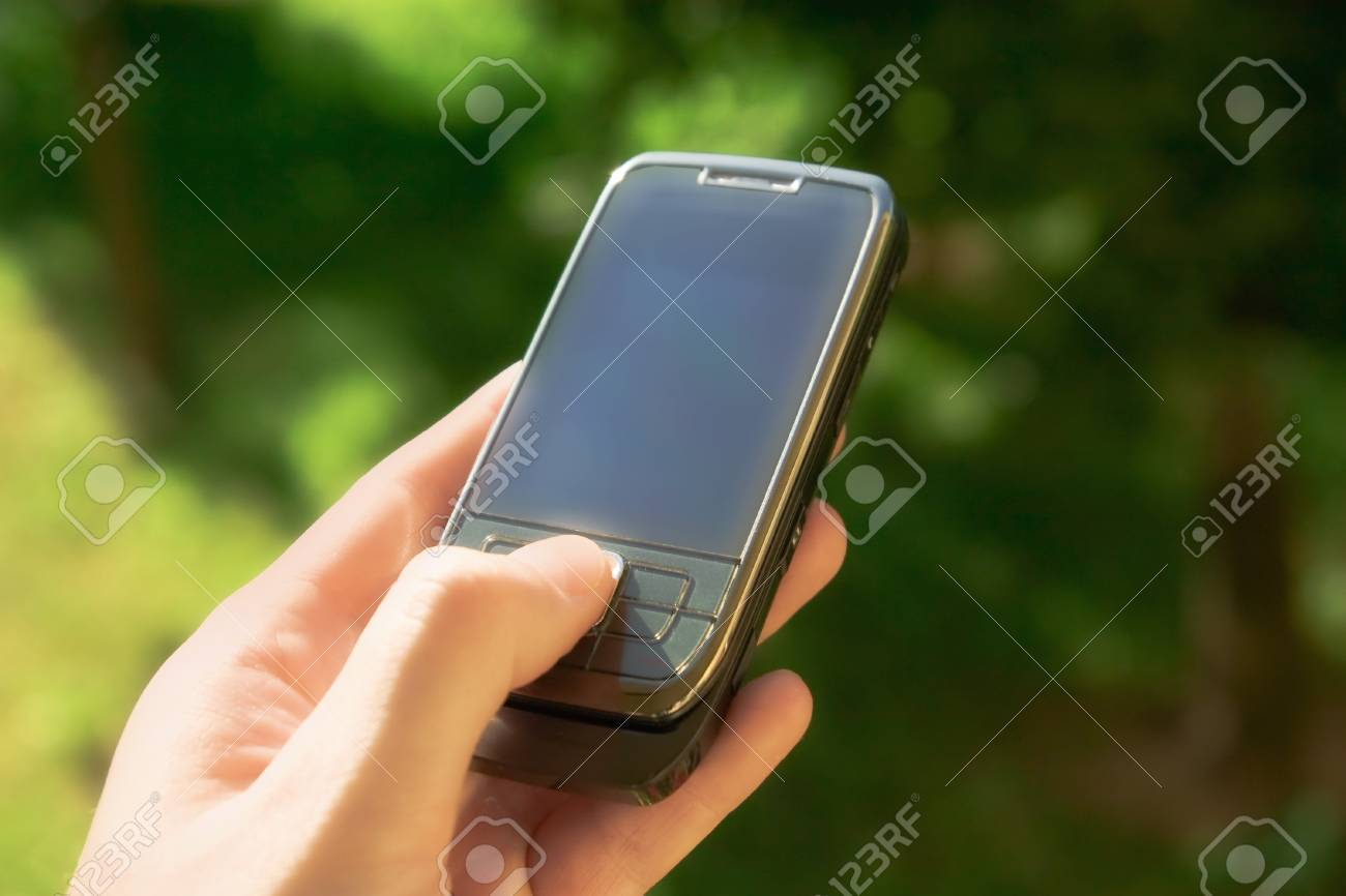 Sleek cell phone in hand with blank blue screen Stock Photo - 13019879
