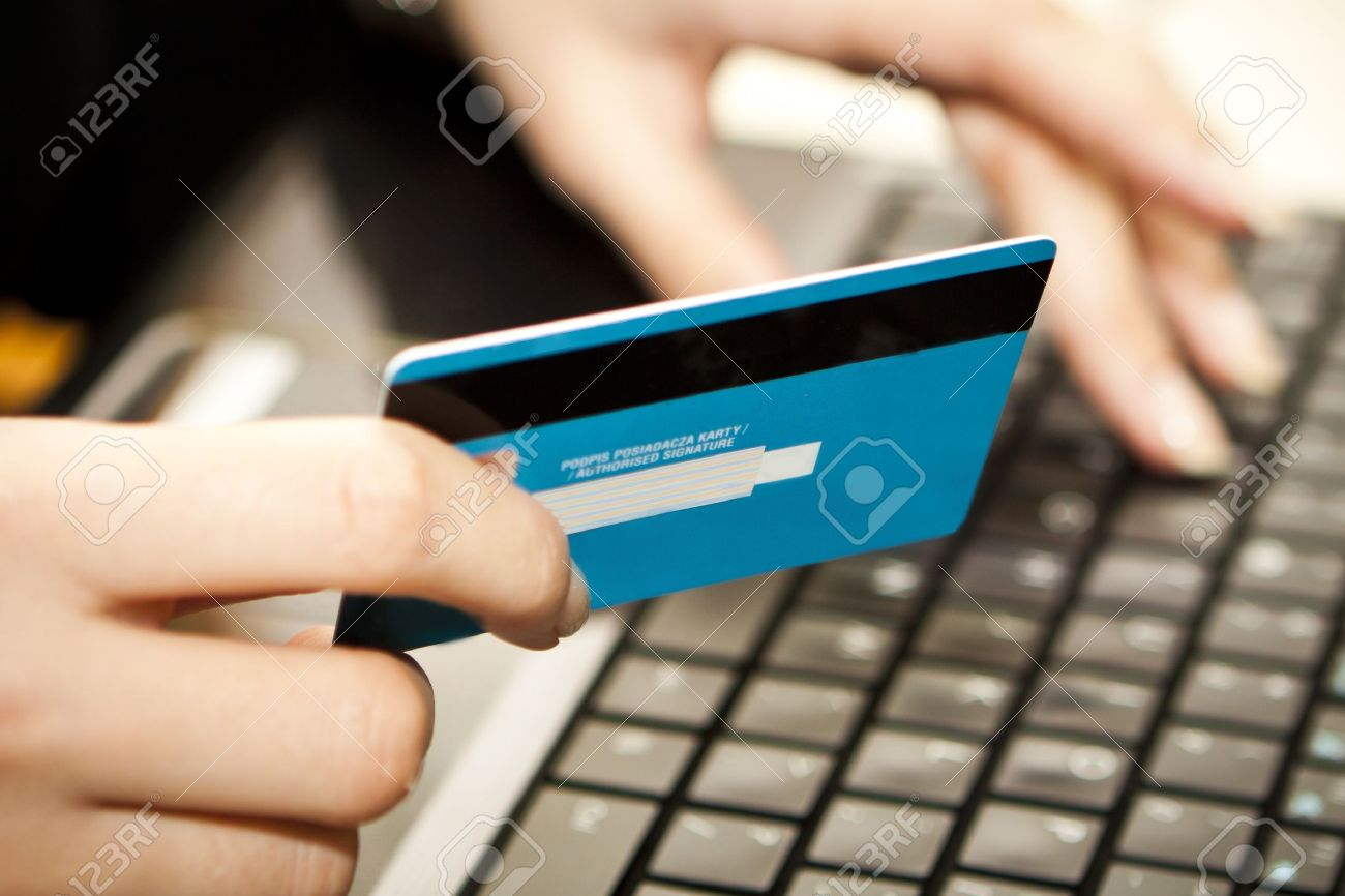 Hands entering credit card information into a laptop Stock Photo - 15056919