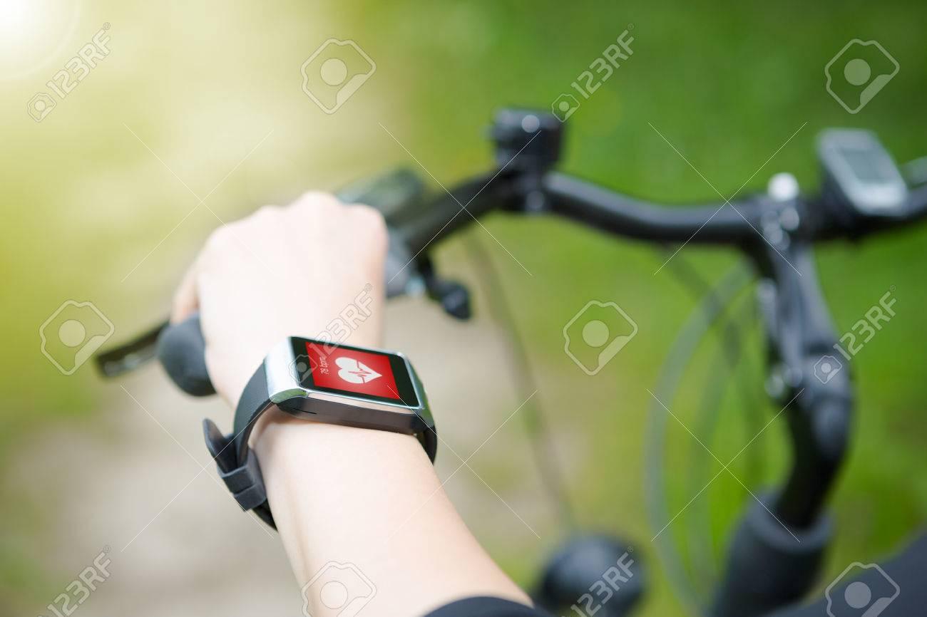 Femme chevauchant un vélo avec un cardiofréquencemètre SmartWatch. Concept de montre intelligente. Banque d'images - 43398553