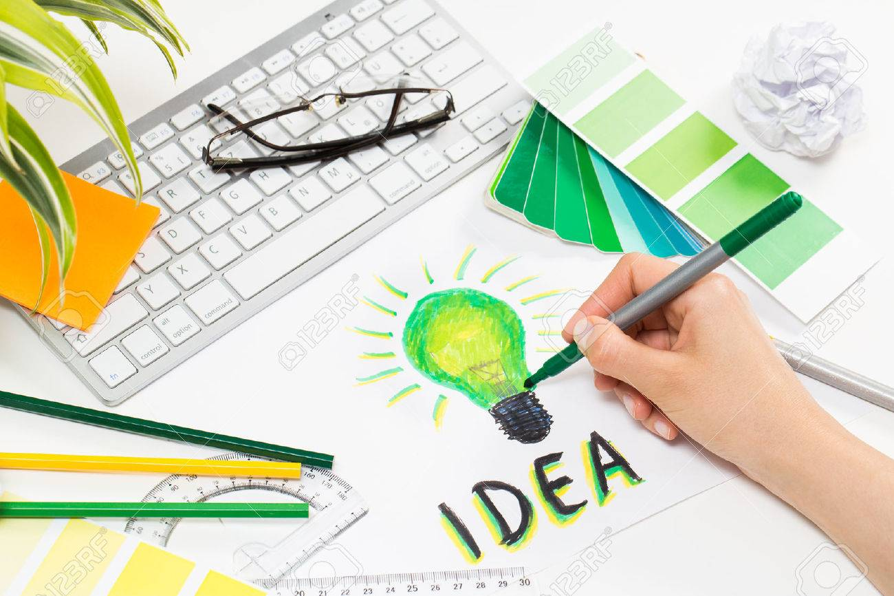 Designer drawing a green light bulb. Brainstorming and inspiration cocnept. Banque d'images - 43398564