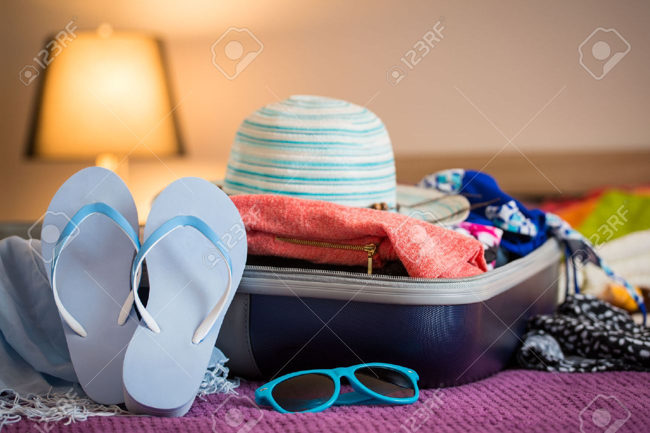 Open suitcase with clothing in the bedroom. Summer holiday concept. Stock Photo - 44883782