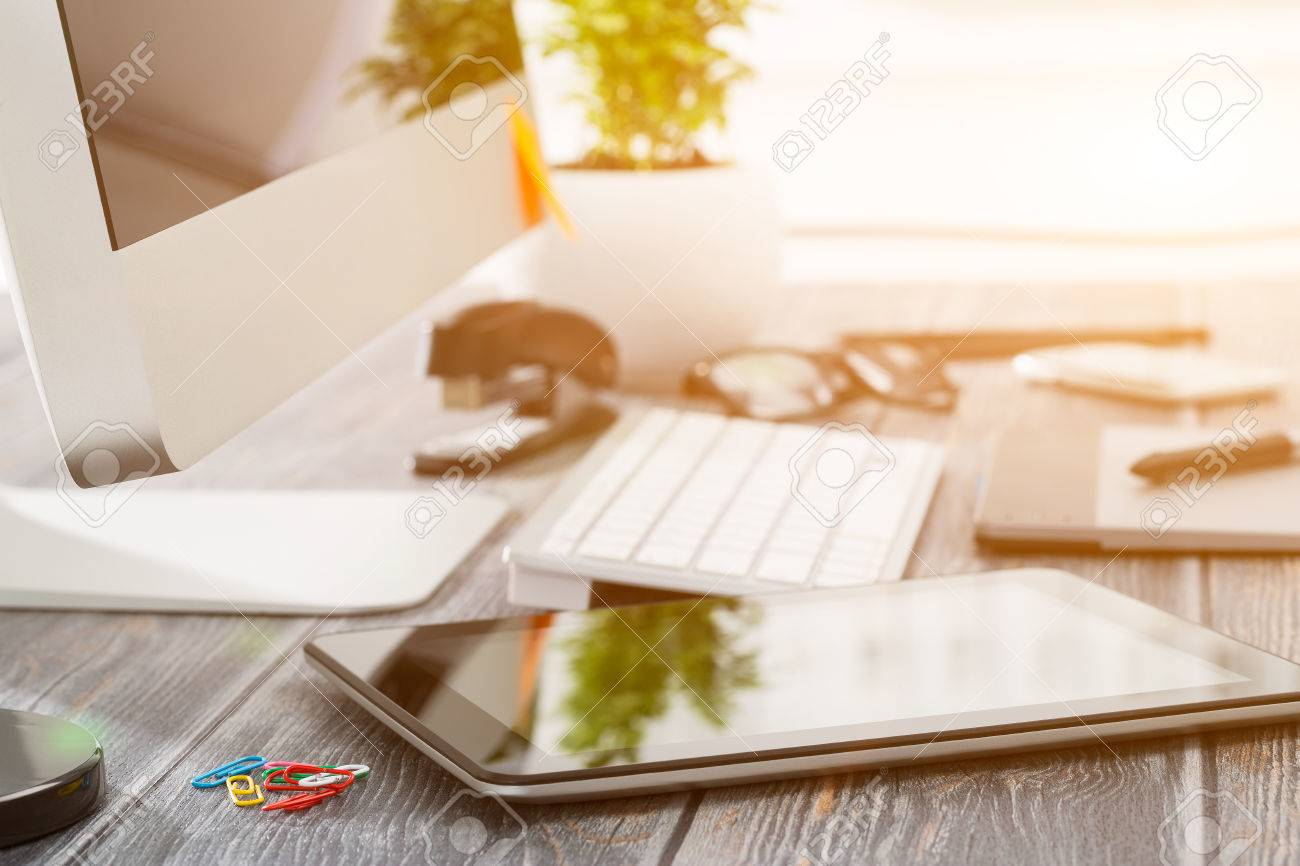 Office workplace with tablet and pc on wood table. Stock Photo - 55613517