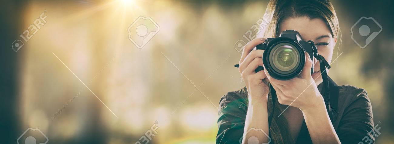 Portrait of a photographer covering her face with the camera. Banque d'images - 73650951