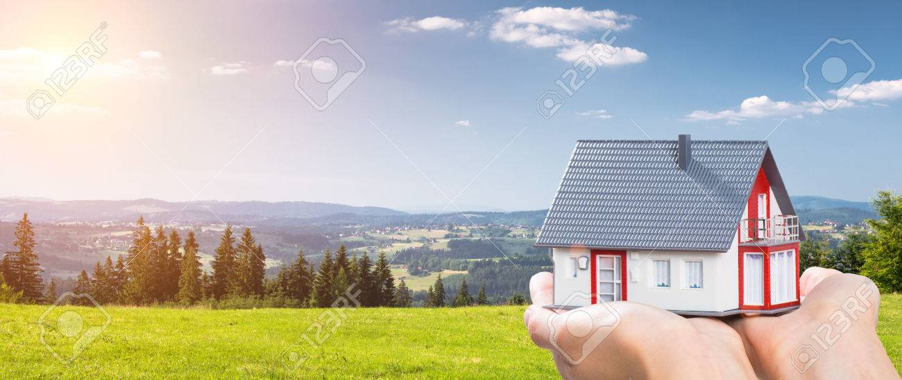 housing house hand real home holding green grass blue sky- stock image Stock Photo - 73650952