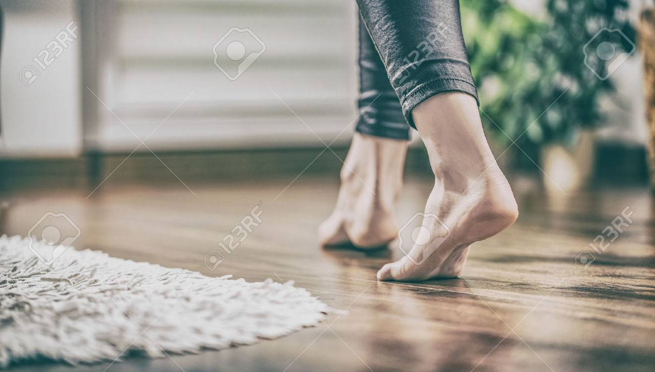 Floor heating. Young woman walking in the house on the warm floor. Gently walked the wooden panels. Stock Photo - 75085995