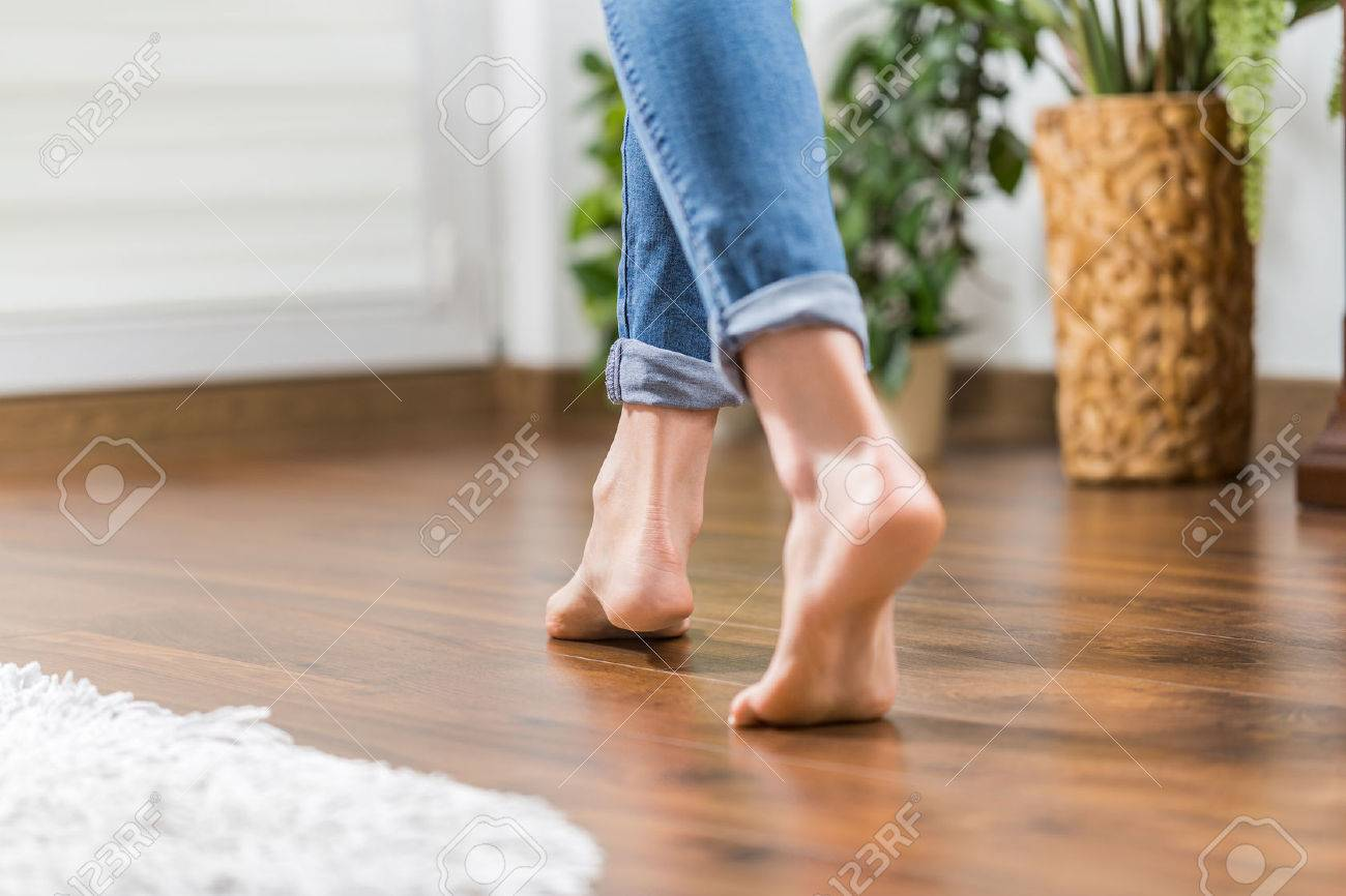 Floor heating. Young woman walking in the house on the warm floor. Gently walked the wooden panels. Stock Photo - 75086017
