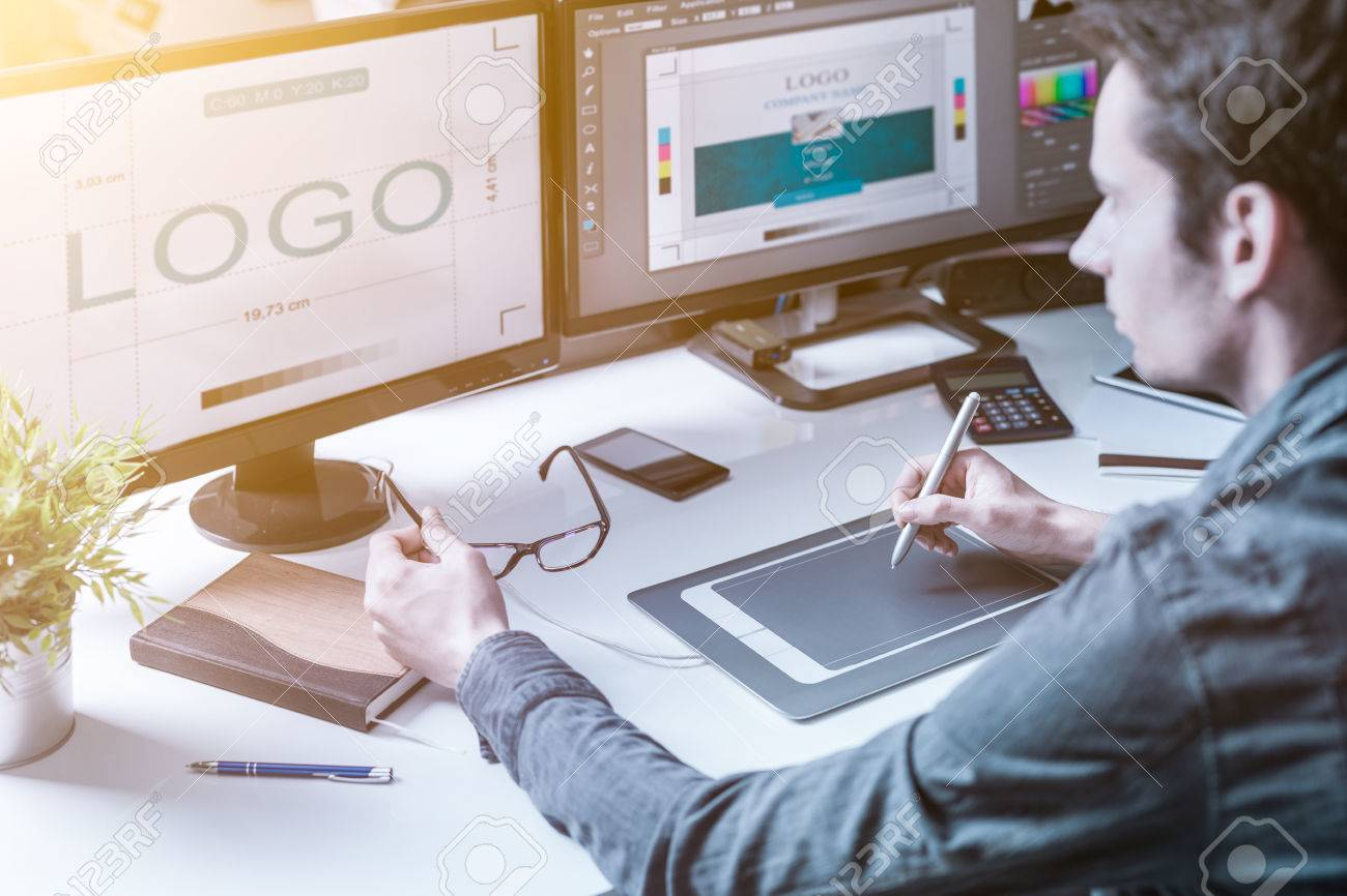 Computer graphic designer designs logos and advertising graphics. Draws a logo on the graphics tablet. - 75086160