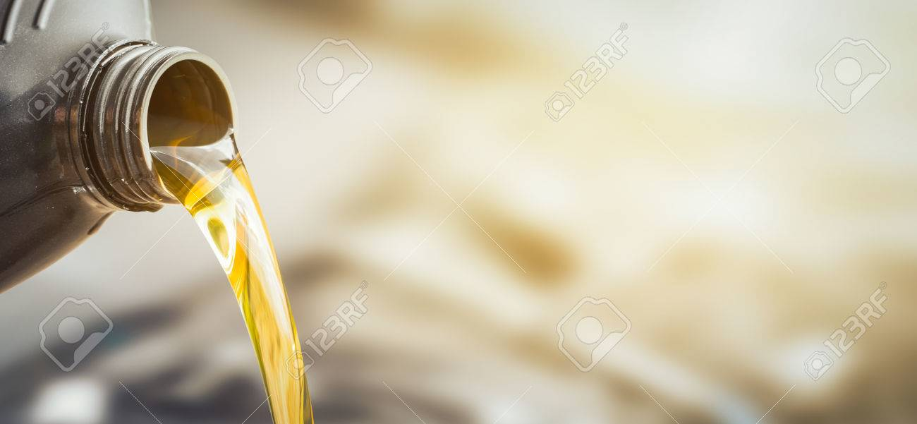 Pouring oil to car engine. Fresh oil poured during an oil change to a car. - 82172148
