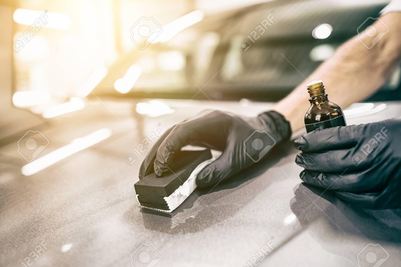 Car detailing - Man applies nano protective coating to the car. Selective focus. - 84412916