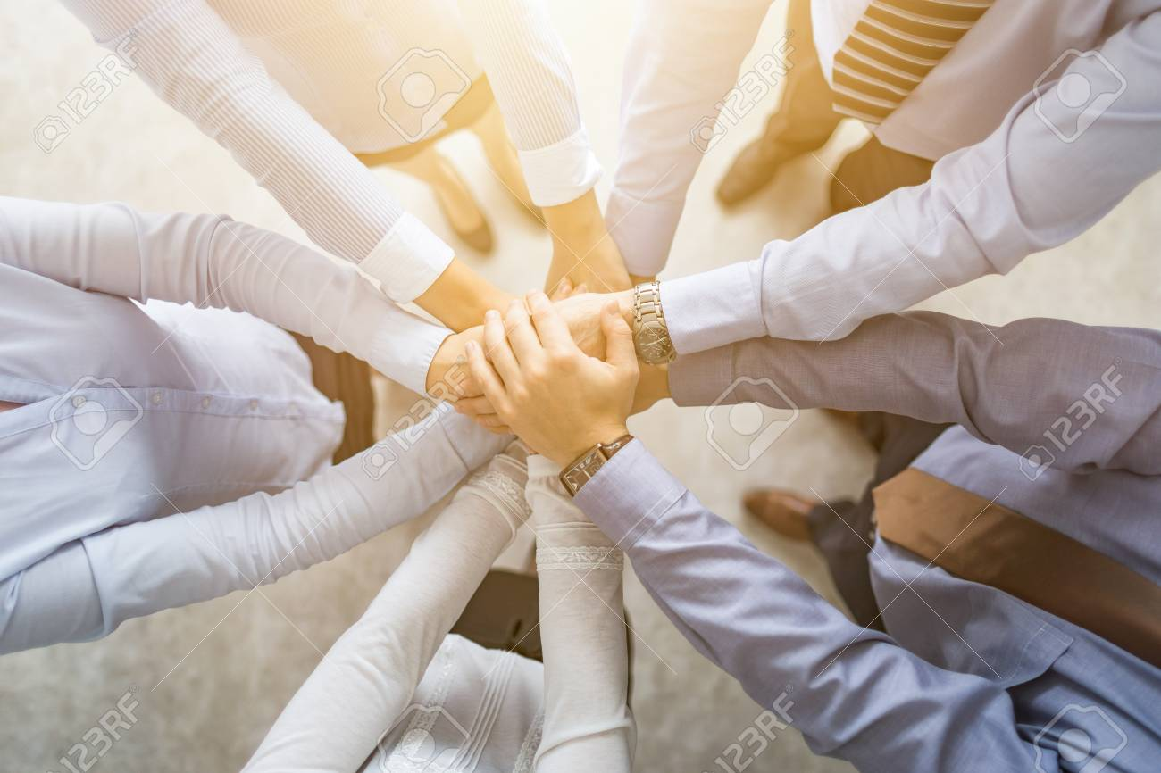 Close up top view of young business people putting their hands together. Stack of hands. Unity and teamwork concept. - 92997455