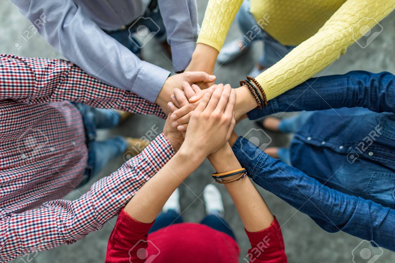 Close up top view of young business people putting their hands together. Stack of hands. Unity and teamwork concept. - 92990605