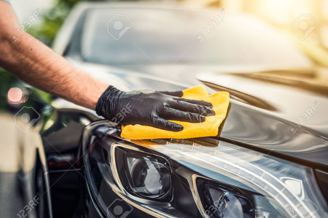 Car detailing - the man holds the microfiber in hand and polishes the car. Selective focus. - 92911016