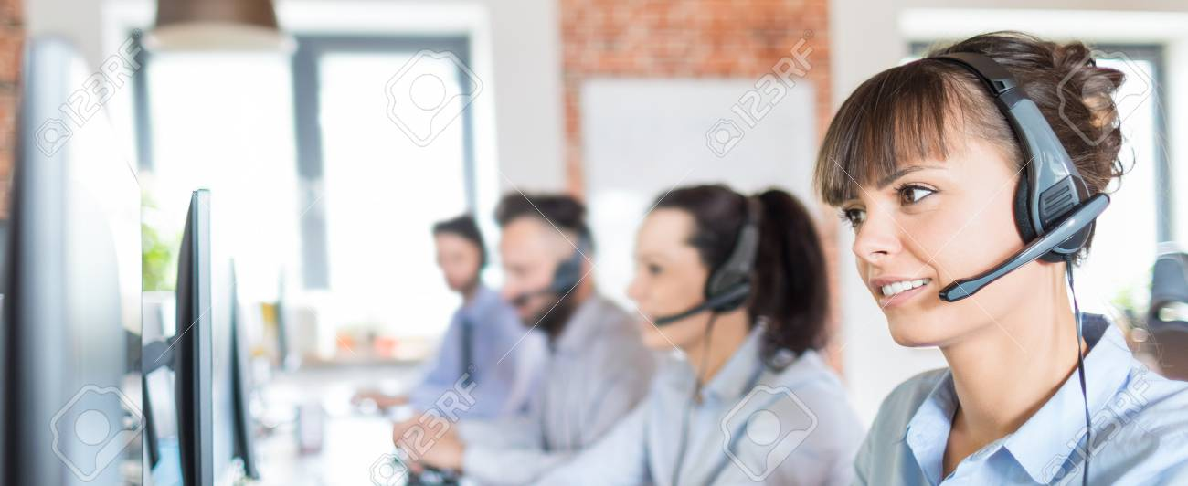 Call center worker accompanied by her team. Smiling customer support operator at work. Young employee working with a headset. - 93002407