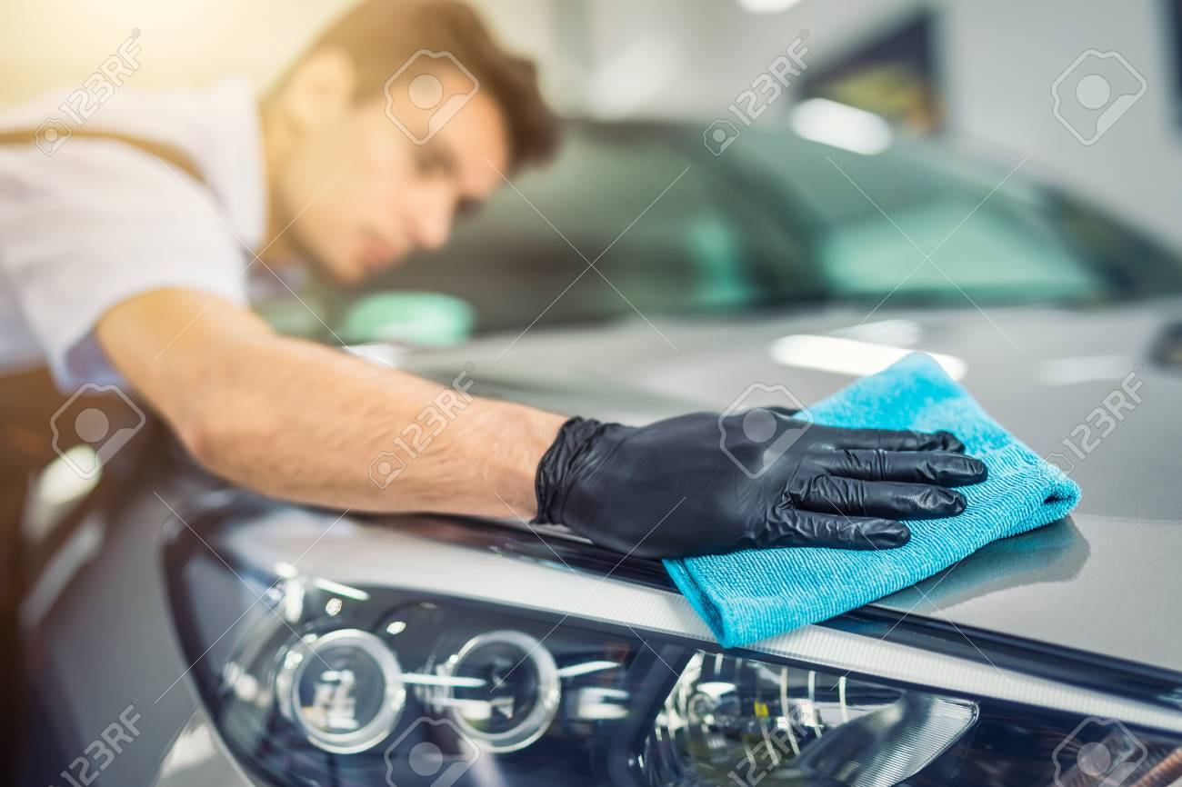 the man holds the microfiber in hand and polishes the car. Selective focus. - 93003371
