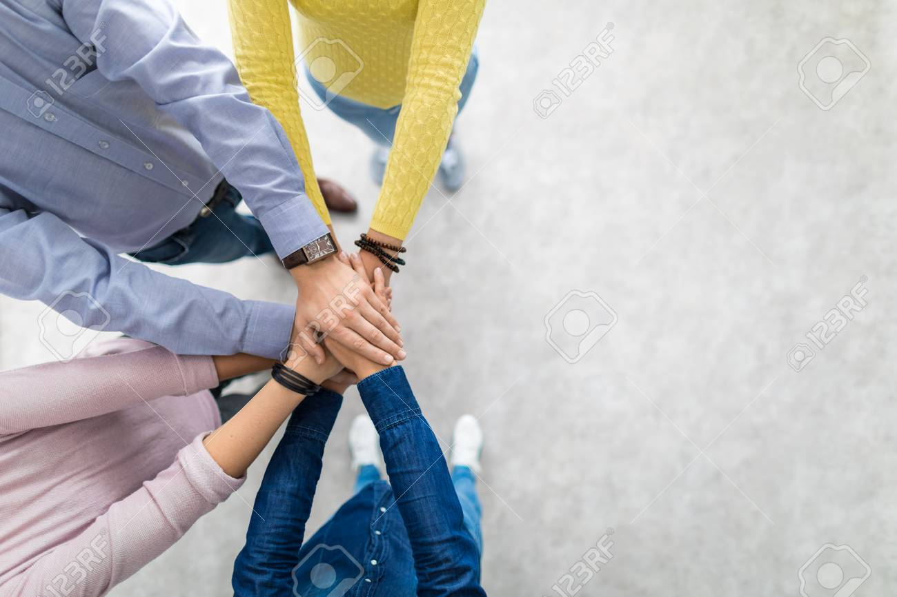 Close up top view of young business people putting their hands together. Stack of hands. Unity and teamwork concept. - 93549824