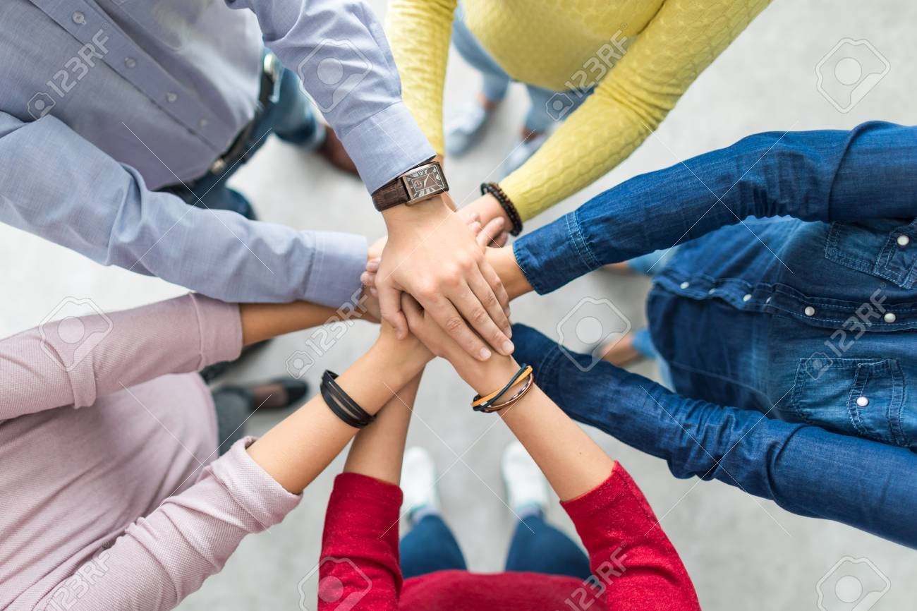 Close up top view of young business people putting their hands together. Stack of hands. Unity and teamwork concept. - 106058173