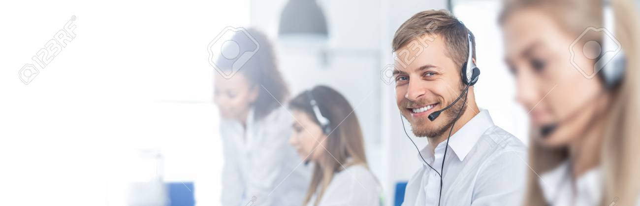 Call center worker accompanied by his team. Smiling customer support operator at work. Young employee working with a headset. - 112532205