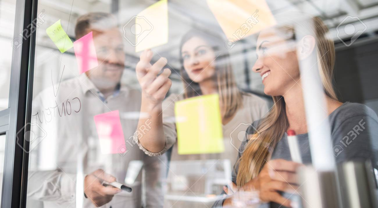 Business people meeting at office and use post it notes to share idea. Brainstorming concept. Sticky note on glass wall. - 113209342