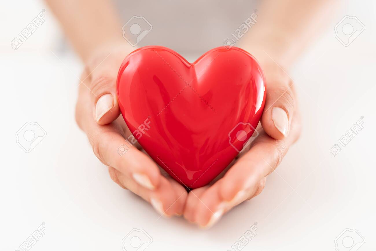 The woman is holding a red heart. Concept for charity, health insurance, love, international cardiology day. - 130848449