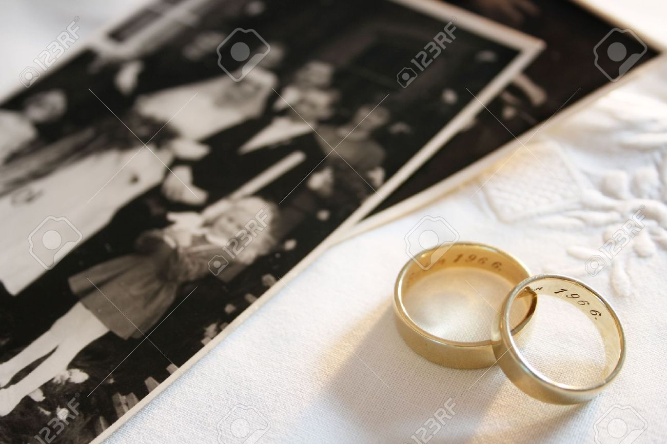 Old Wedding Rings And Out Of Focus Black And White Photograph Of A Wedding  Stock Photo