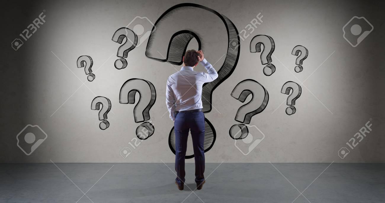 Businessman in modern interior watching question marks sketch
