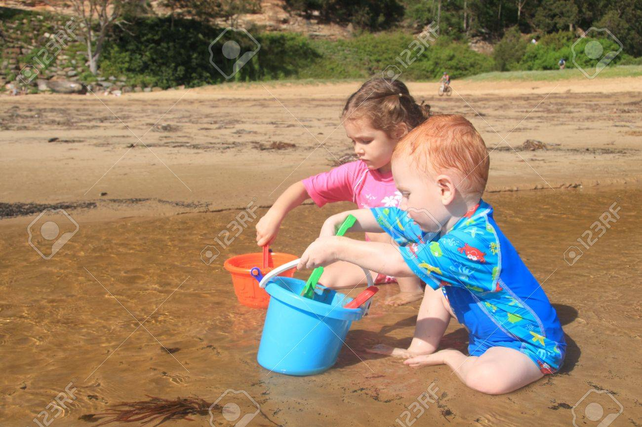 Boy and girl playing in water with buckets and spades on beach Stock Photo - 4545478