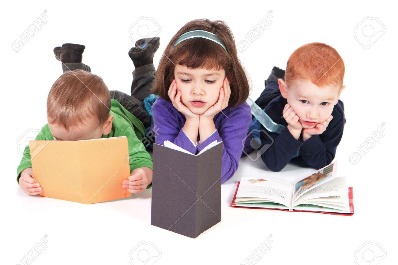 Three kids reading books lying on floor - 7369055