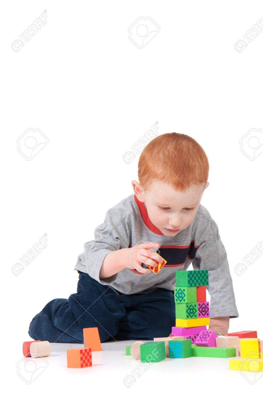 Boy building colorful block tower. Isolated on white with shadows. - 7596249