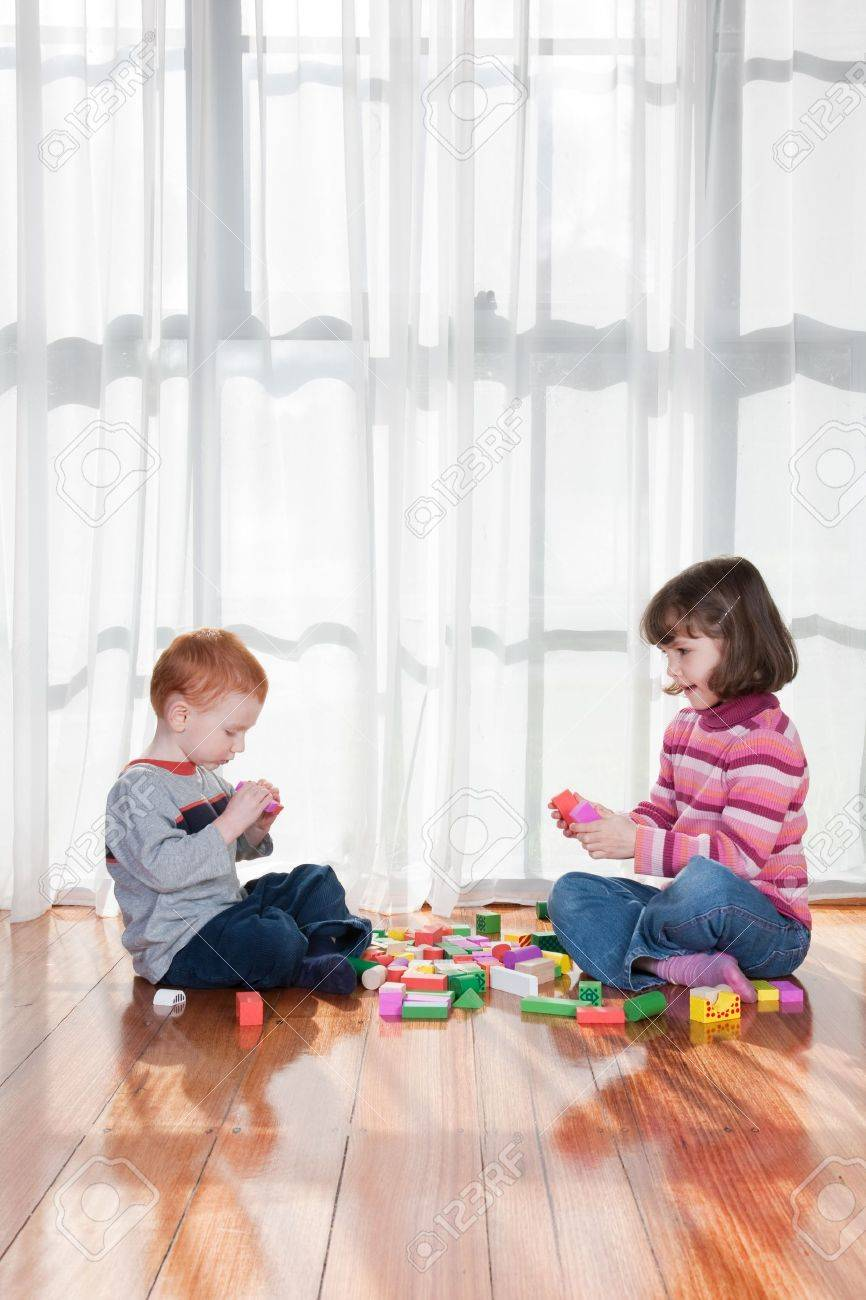 Two kids playing with wooden blocks in front of window - 7596257