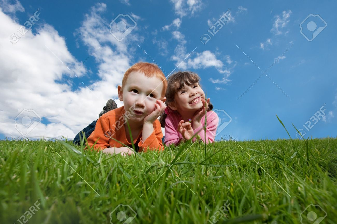Two kids lying on top of grassy hill with blue sky background - 8218937