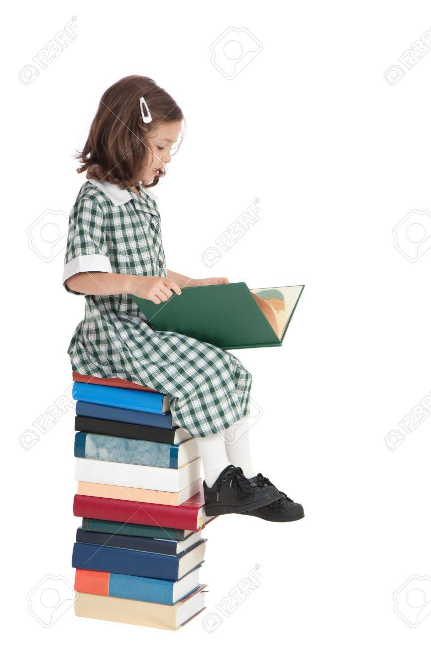School girl in uniform sitting on stack of books reading. Isolated on white. - 8723946