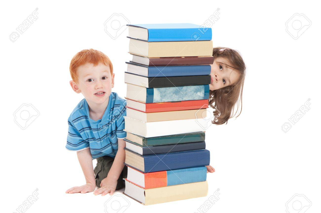 Two kids hiding behind stack of books. Isolated on white. - 8723945
