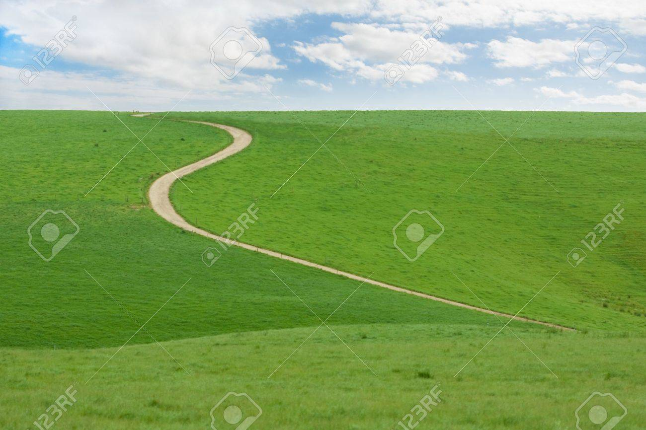 Winding dirt road going up green hill with blue cloudy sky - 8723950