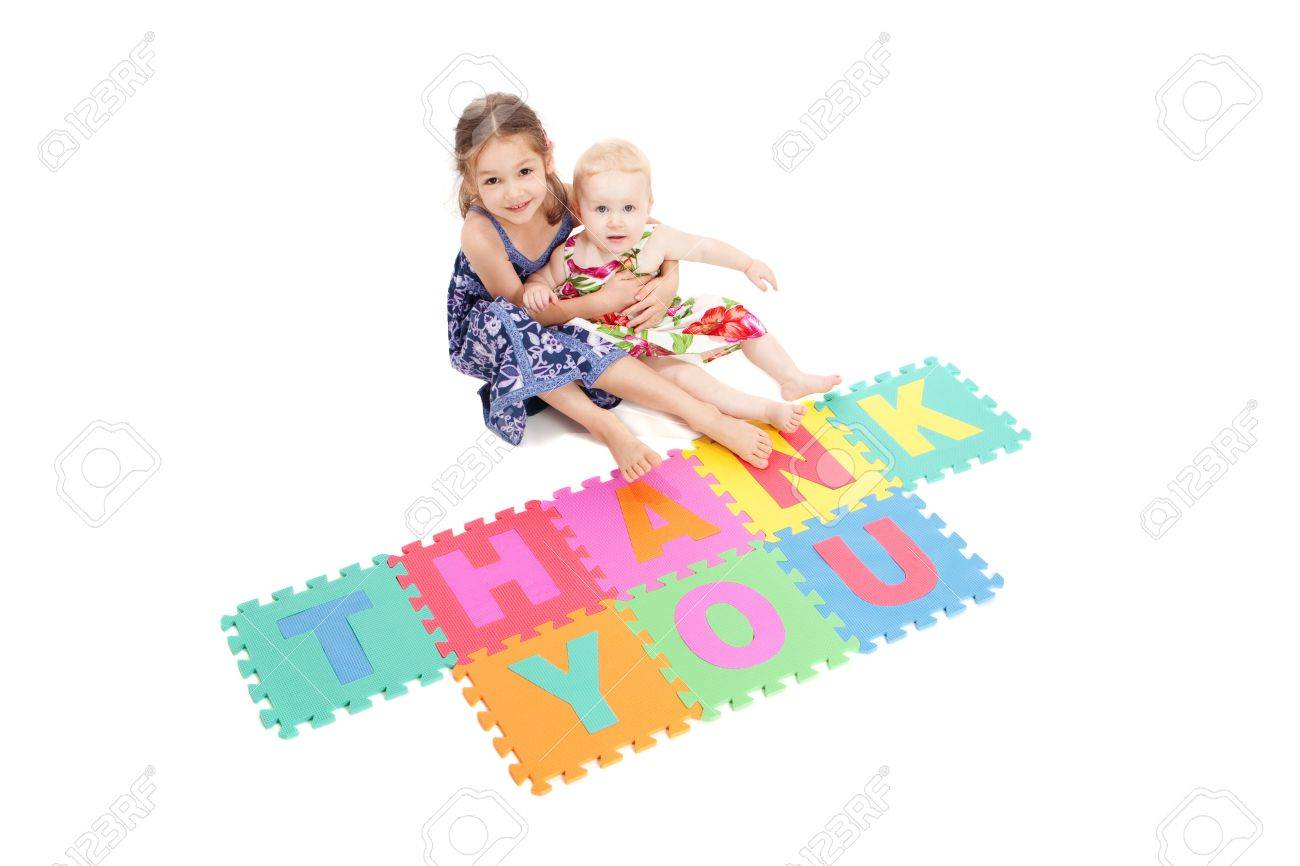Two girls saying thankyou with letter tiles. Isolated on white. - 8927079