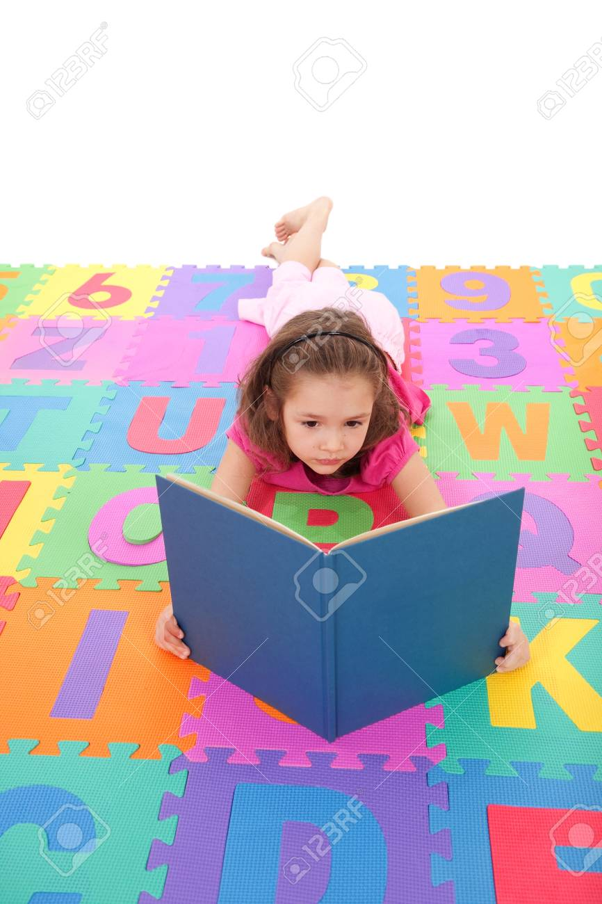 Young girl reading book on alphabet floor mat. Isolated on white. Stock Photo - 9080040