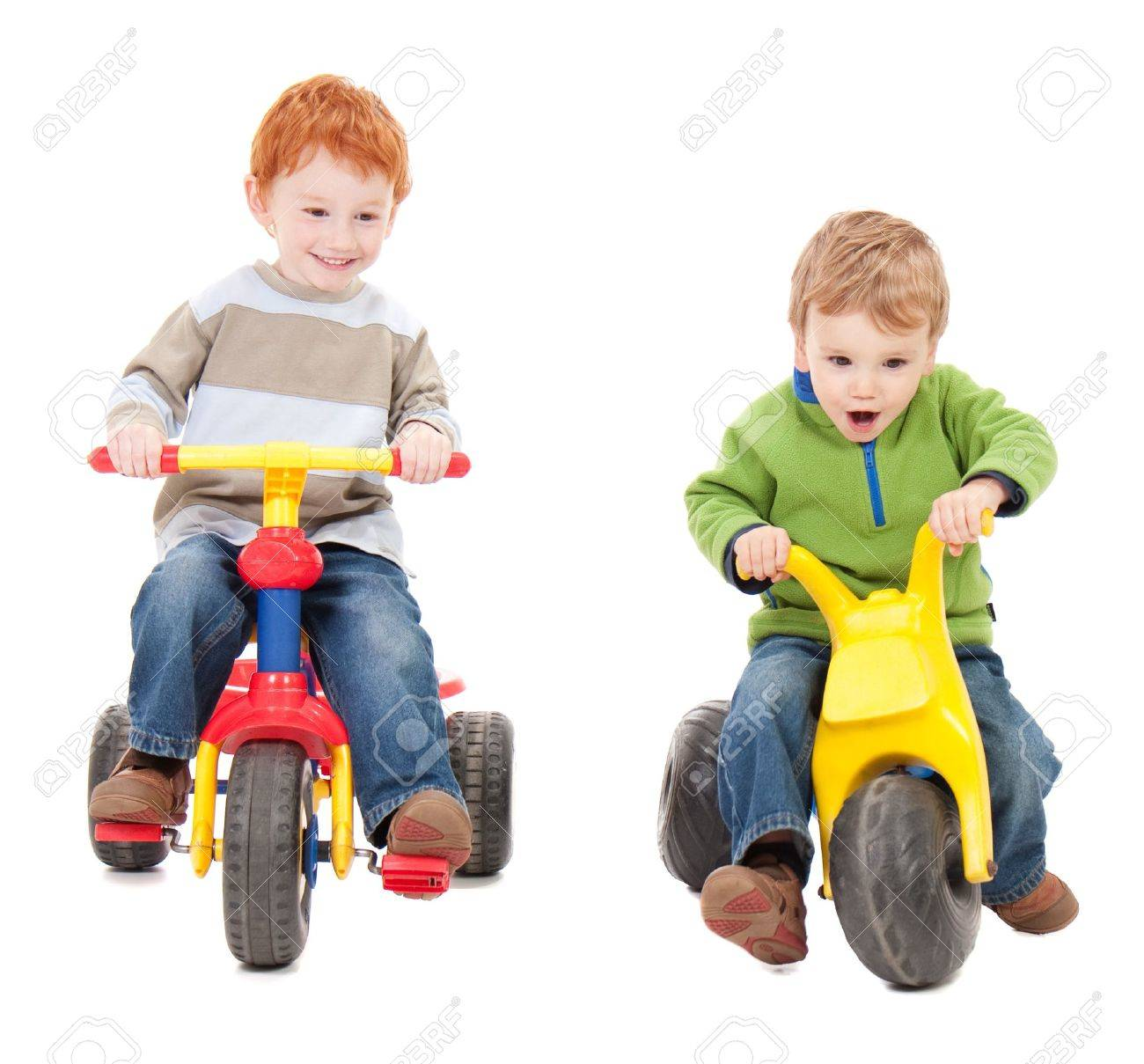 Children riding trycycles. Isolated on white. - 9334517