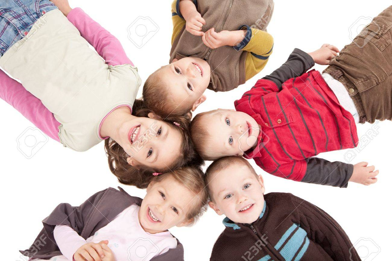 Group of happy kids lying on backs on isolated white floor. - 9699035