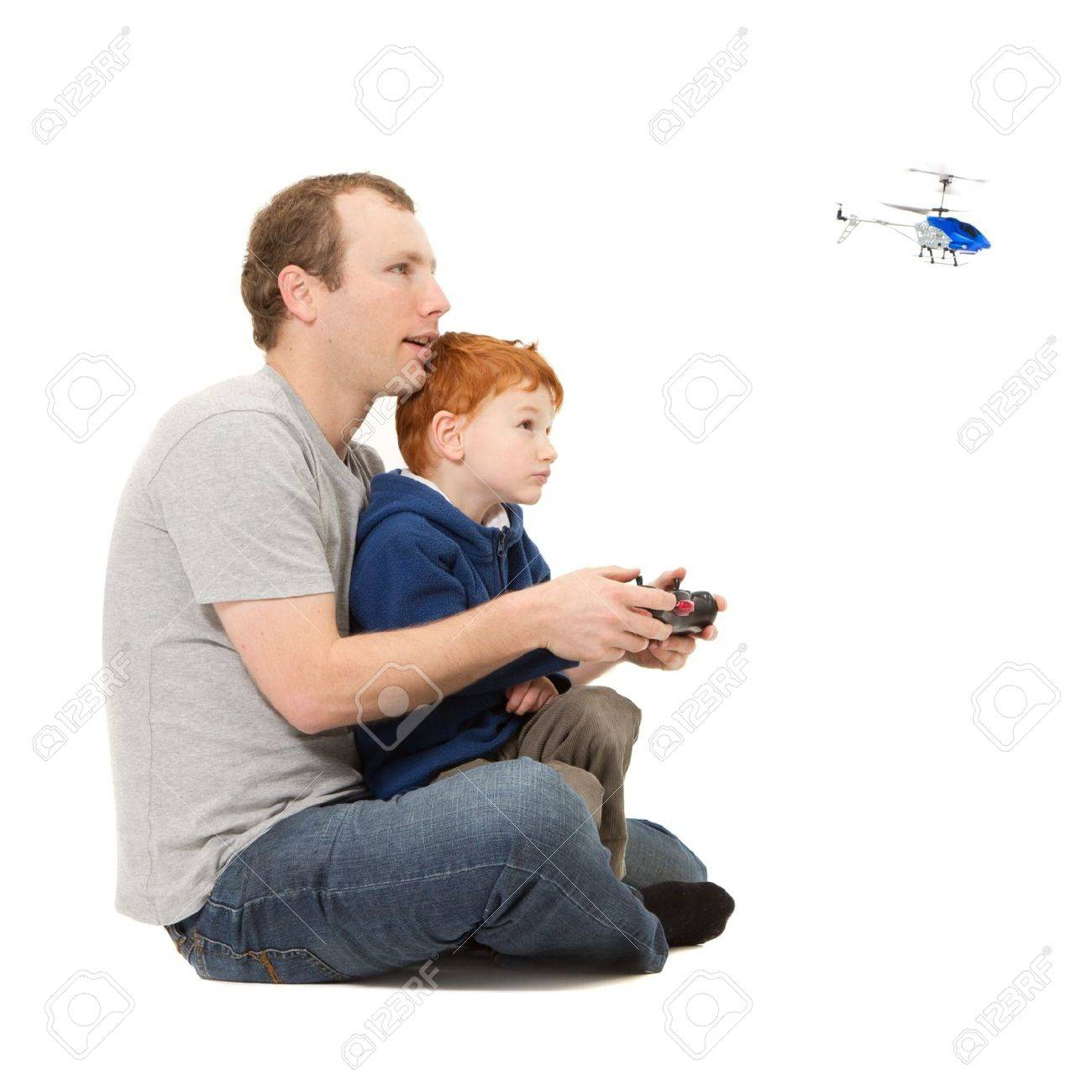 Father and son spending time playing together flying radio controlled helicopter - 15155159
