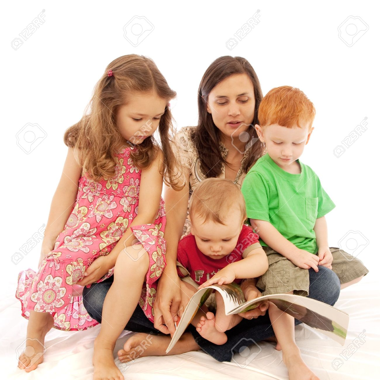 Mum reading to three young kids on her lap - 15155171