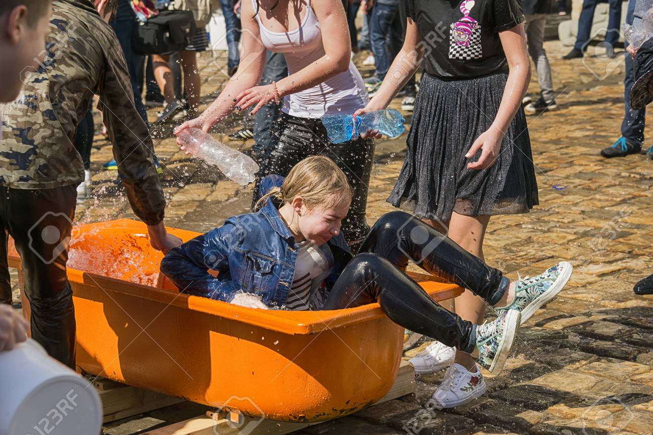 Lviv , Ukraine - April 09 2018: Ð¡elebrations Wet Monday, a Ukrainian Christian tradition celebrated on the first day after Orthodox Easter. Wet girl gets up from the bath near the town hall. Lviv, Ukraine. - 104325856
