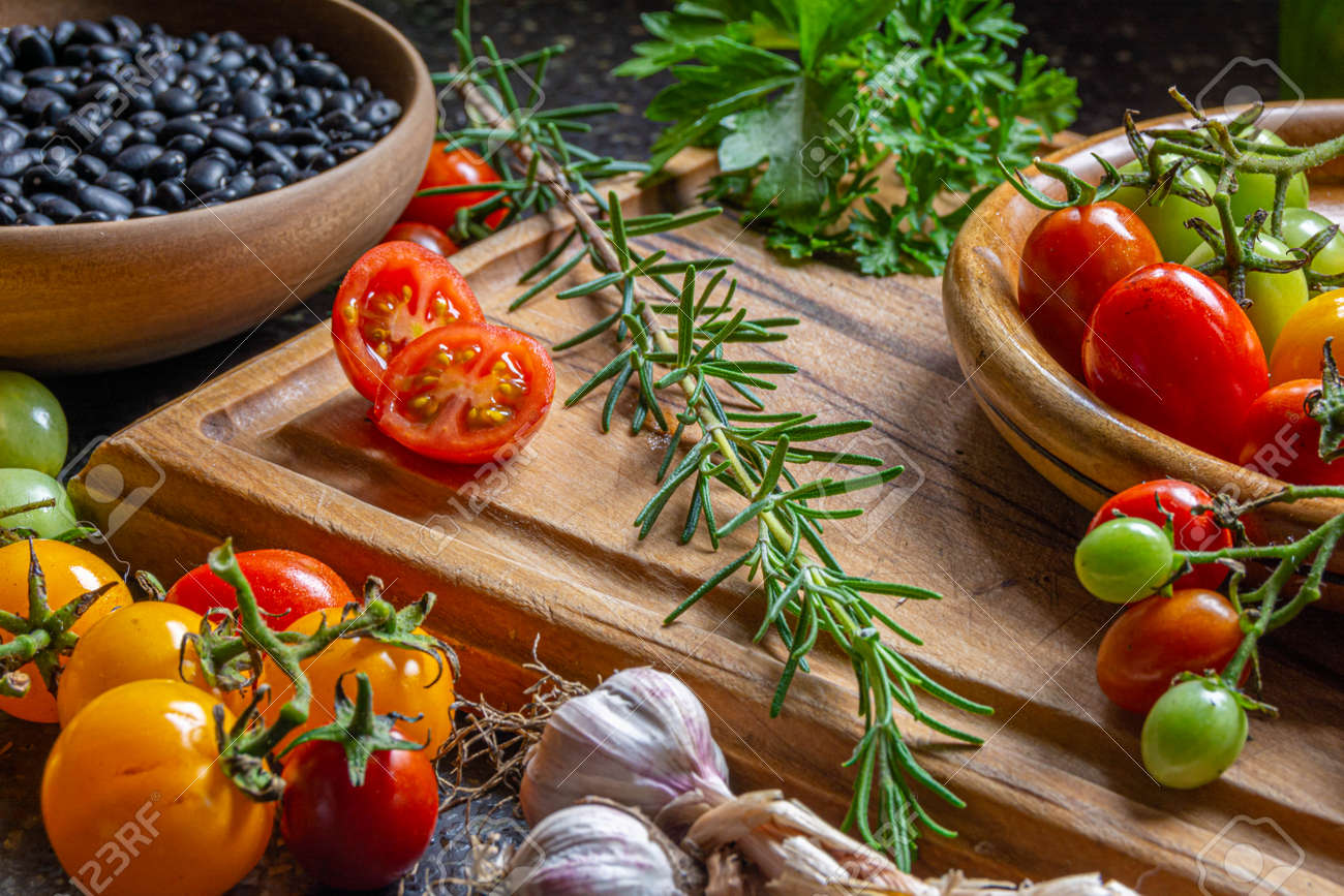 Fresh organic vegetables and ingredients on a wooden cutting board - 166541560