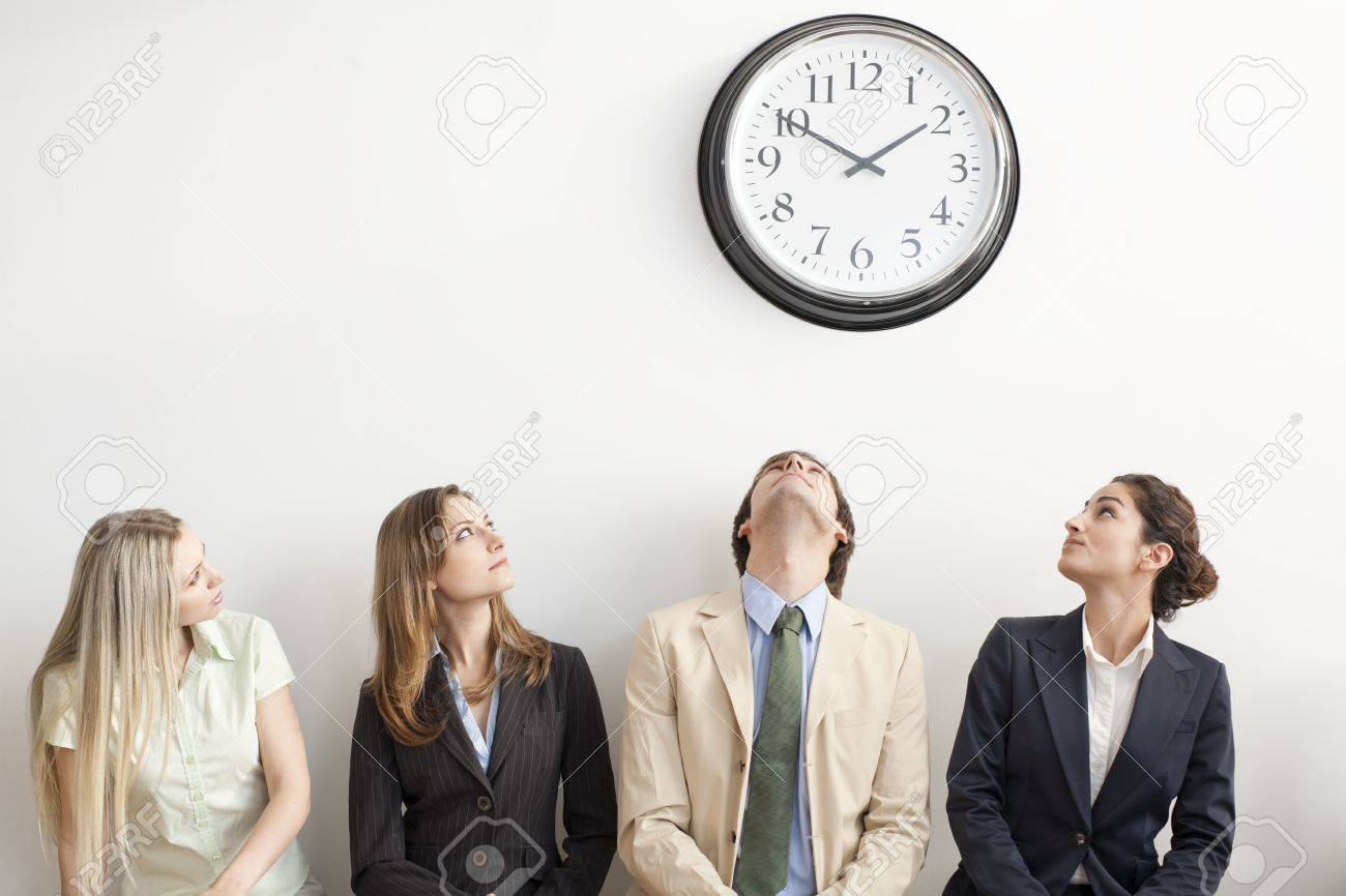 four businesspersons sitting on bench looking up at clock
